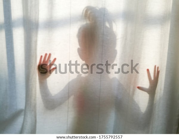Silhouette of a little girl hiding behind a white curtain.