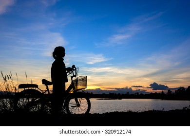 Silhouette of little girl on a bicycle with sunset