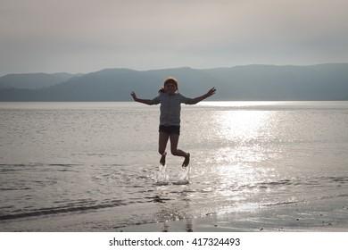 silhouette of little girl playing in the sea at sundown, Opoutama Beach, Mahia Peninsula, East Coast, North Island, New Zealand