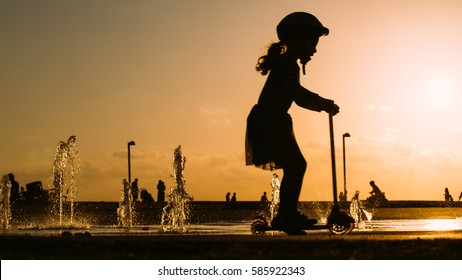 silhouette of a little girl riding a scooter through water fountains in a sundowner (tel aviv, Israel)