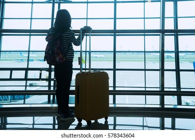 Silhouette of little girl standing in the airport while carrying bag and looking at aircraft on the window