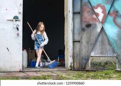 Silhouette of a little girl sweeping the broom in the open door of the warehouse - a hard working child in a dirty place