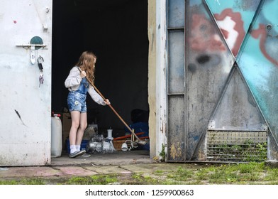 Silhouette of a little girl sweeping the broom in the open door of the warehouse - a hard working child