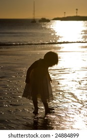 Silhouette of a little girl in a white dress on the beach at sunset.  The ocean and sunset is in the background.