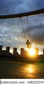 Silhouette of a little happy girl on a swing against urban landscape in a city park at dawn. Dramatic sky over playground. Inspirational photo. Childhood and hope concept. Copy space for text.