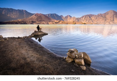 Silhouette of local people at Segara Anak Lake in early morning. Mount Rinjani is an active volcano in Lombok, Indonesia. Soft focus due to long exposure.