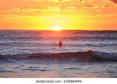 Silhouette of lone male surfer sitting on surfboard at sunrise facing the sun
