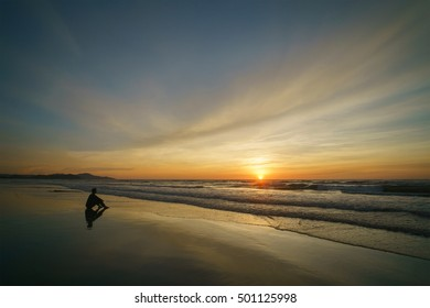Silhouette of lone man sitting at the beach alone watching the sun setting into sea horizon.