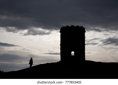 Silhouette of lone walker at Solomon's in Buxton, Derbyshire on a cold windy day against a dramatic dark sky.