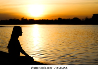 silhouette of lonely asian woman sit alone in the park,Sad thai woman think something,Heartbreak girl concept,sunset
