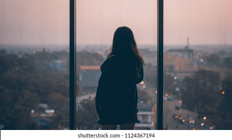 Silhouette of lonely girl looking outside