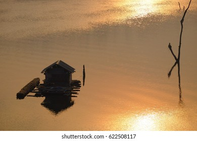 A silhouette lonely little house in the river with sun rising