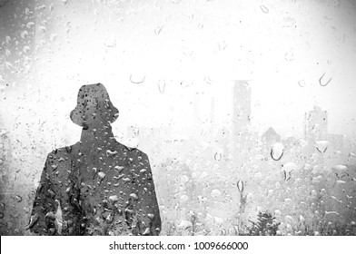 Silhouette of lonely man with hat and city skyline behind wet glass of rain. Black and white tone.