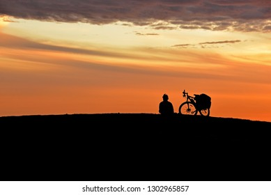 Silhouette of lonely man with his bicycle during sunset time.Beautiful sky with copy space.Concept about loneliness and expectation.Waiting for someone.