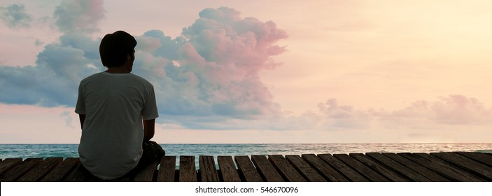 Silhouette Lonely Man sitting in a wooden dock pier in sea beach with twilight sky in sunset time and think concentrate