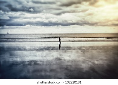 SIlhouette of a lonely person walking on a beach at low tide. Reflection of the clouds in the damp sand. This image was taken in Hendaye (Pays Basque, France).