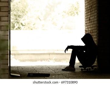 Silhouette of  Lonely Teenager Sitting in the Dark Doorway  in a Sweatshirt with a Hood