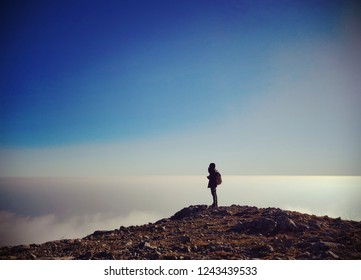 Silhouette of a lonely tourist on the top of a mountain