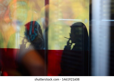 Silhouette of lonely woman smoking a cigarette