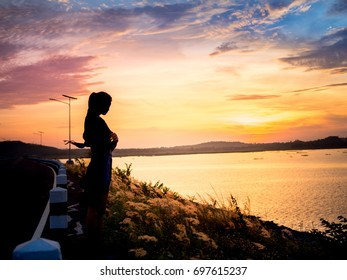 silhouette of lonely woman standing near the river at sunset