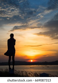 silhouette of lonely woman  standing at sunset