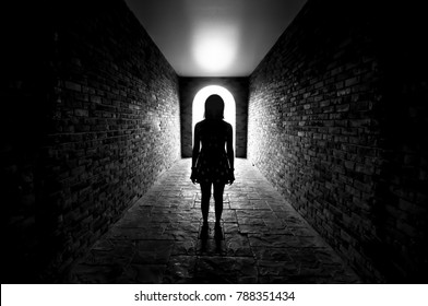 Silhouette of Lonely woman standing in the tunnel and Light at the end of the tunnel.