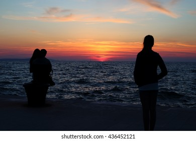 Silhouette of a lonely womanl looking at a her boyfriend cheating on her with another woman upon sunset at the seaside, their relationship is sinking like the setting sun