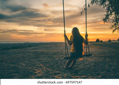 The silhouette of a lonely young woman swaying at the beach at sunset