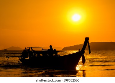 silhouette Long tail boat with sunset time