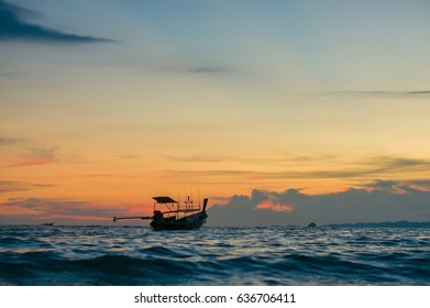 Silhouette of longtail boat in ocean on sunset