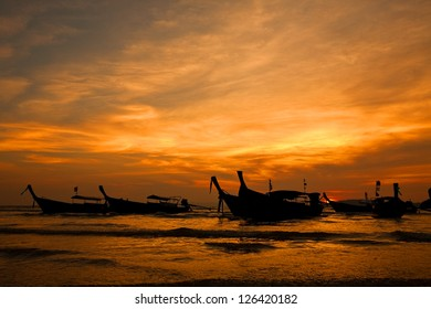 Silhouette of longtail boats at the beach on sunset in Thailand