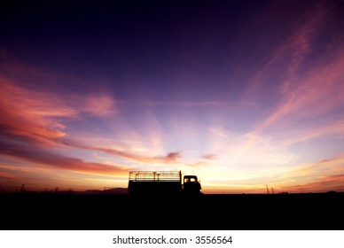 Silhouette of lorry during sunset by the highway