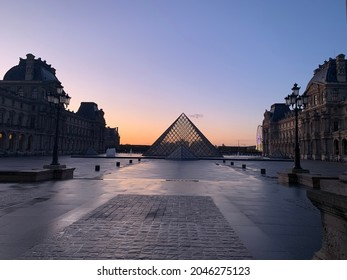 Silhouette of the Louvre in Paris France, with the sunset spilling its last golden rays of light faintly onto the courtyard.