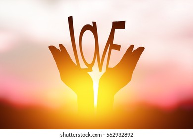 Silhouette LOVE in hand. Background sunrise