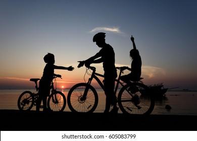 Silhouette lovely family at sunset over the ocean, biker family.