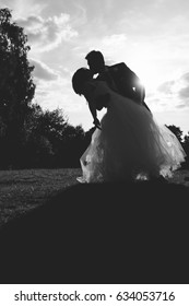 Silhouette of a lovely married couple kissing each other passionately at sunset in black and white