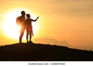 The silhouette of a lover, holding hands on the hills, couples with sunrise or sunset, happy couple man and woman tourist, asian tourist backpacker with sunset