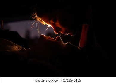 Silhouette of lovers in the car in the back seat. Loving couple retired at dusk to spend the evening together. The girl bent to kiss the guy who is lying below and looking into her eyes. Passion