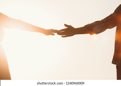 Silhouette of lovers hands stretching towards each other against sunset, copy space