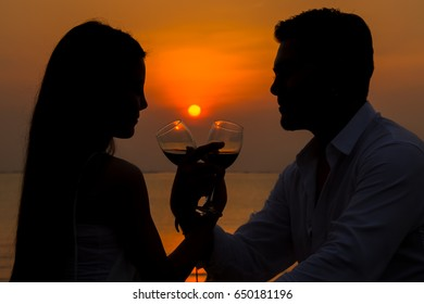 silhouette Lovers smash a glass of wine on a sunset on the beach