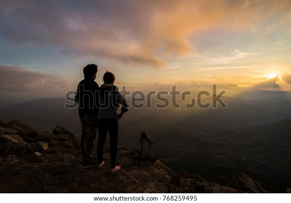Silhouette of loving couple embracing on the mountain against colorful sky at sunset.