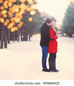 Silhouette of loving couple embracing in warm winter day, christmas lights bokeh, vintage soft colors