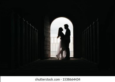 Silhouette of loving couple hugging while standing in doorway on black background, Bride and groom in wedding day posing in a doorway