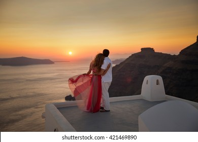 Silhouette of a loving couple on the background of the setting sun, mountains, islands and sea. Santorini. Greece. Just married. Walk at sunset. Walk through the mountains at sunset. Santorini sunset