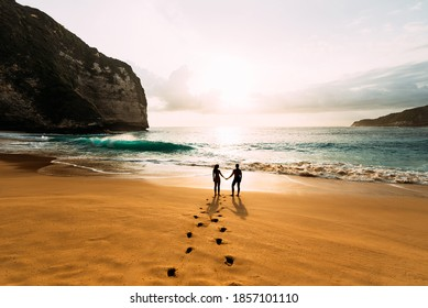 Silhouette of loving couple on sea. A couple in love at sunset. Man and woman meet sunset. Happy loving couple. Silhouette lovers. Man and woman watching the sunset. Hold hands. Copy space
