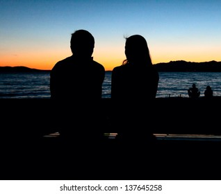 silhouette of a loving couple sitting on a bench at sunset