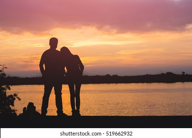 Silhouette of loving couple standing riverside and beautiful sunset background.