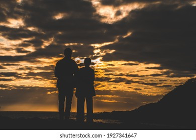 Silhouette of loving couple at sunrise. Man and woman holding hands on the seashore. Love and romance