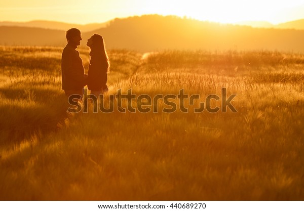 Silhouette of a loving couple at sunrise in a wheat field. Postcard or wallpaper with love, relationship theme