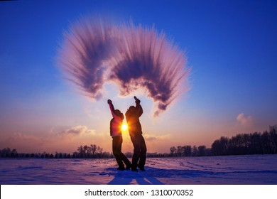 Silhouette of a loving couple at sunset in winter. Spit boiling water in the cold